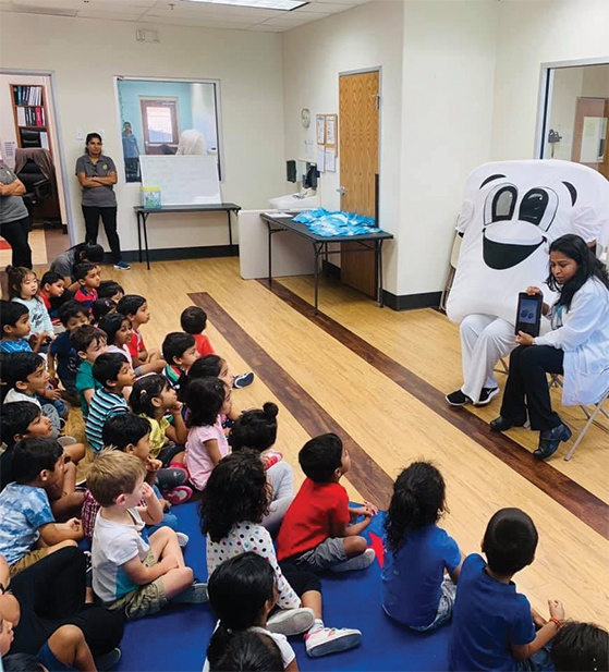 Dentist and tooth mascot teaching kids