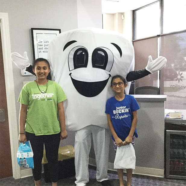 Two young people with tooth mascot