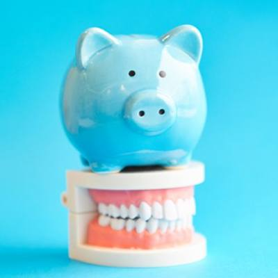 blue piggy bank sitting on top of set of fake teeth against blue background