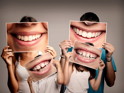 Family holding portraits of smiles at their Guardian dentist.