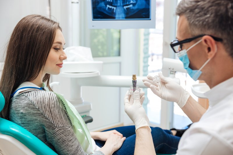 Dentist explaining a dental implant to patient