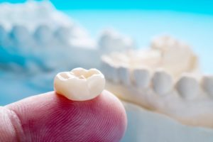 Restoration sitting on fingertip, models of dental crowns behind it