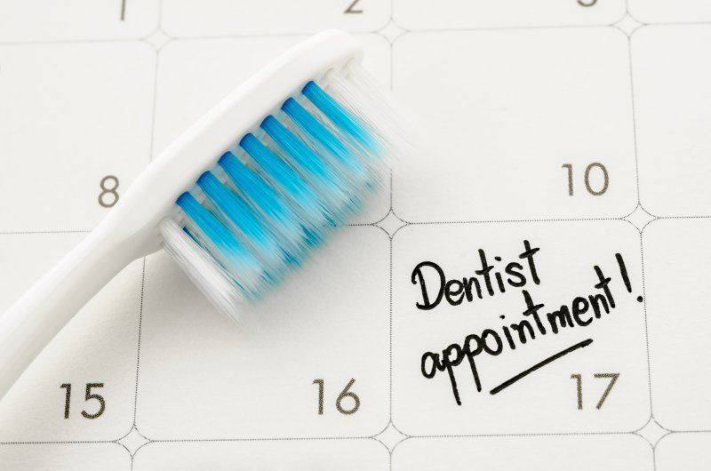 "an image of a toothbrush lying on a calendar with ""Dentist Appointment"" written on one of the dates"